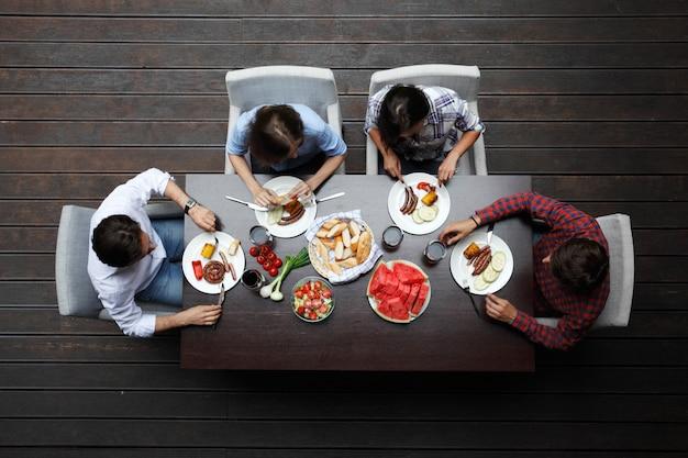 Due giovani coppie che mangiano la cena dietro la tavola