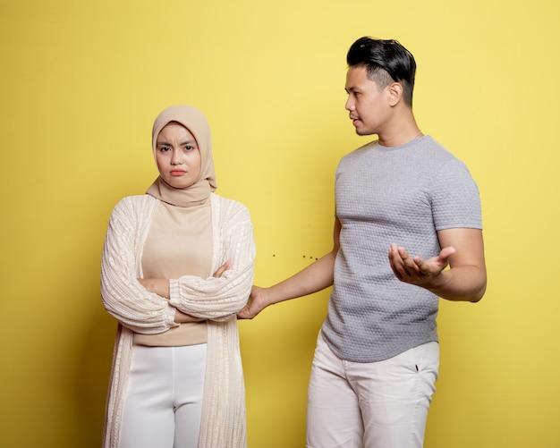 Due giovani coppie in un problema. un uomo che chiede alle donne cosa c'è di sbagliato isolato su sfondo giallo
