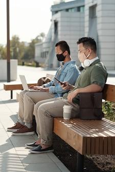 Due giovani colleghi con gadget mobili seduti su una panchina