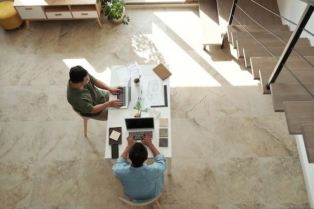 Due giovani designer o architetti che digitano su laptop