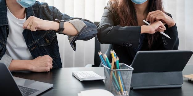 Due giovani colleghi di lavoro diversi che indossano maschere protettive per il viso urtano i gomiti, salutandosi mentre lavorano durante la quarantena del covid 19.
