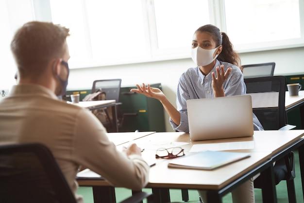 Due giovani colleghi diversi che indossano una maschera protettiva per il viso discutono di qualcosa mentre lavorano
