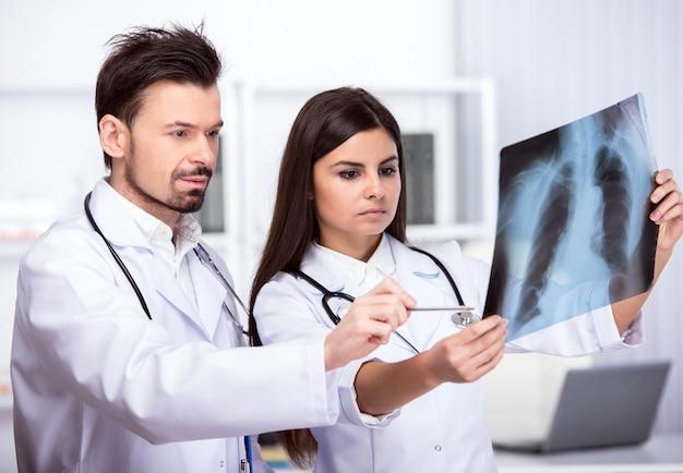 Due giovani medici stanno esaminando i raggi x in studio medico.