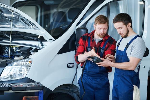 Due giovani ingegneri del centro di assistenza riparazione cura discutendo i dati nel dispositivo elettronico al lavoro