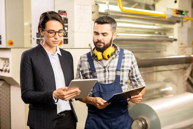 Due giovani ingegneri in piedi accanto alla macchina di elaborazione e testando un nuovo sistema di controllo qualità o guardando i dati