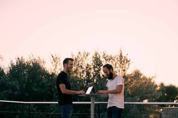 Due giovani imprenditori che hanno una riunione di lavoro mentre lavorano online con i loro tablet