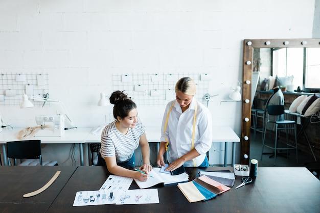 Due giovani stilisti in abbigliamento casual in piedi a tavola mentre scelgono campioni tessili per la nuova collezione stagionale