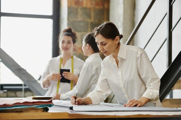 Due giovani designer femminili di vestiti che telefonano ai clienti sugli ordini mentre il loro collega misura la lunghezza dei modelli di carta vicino