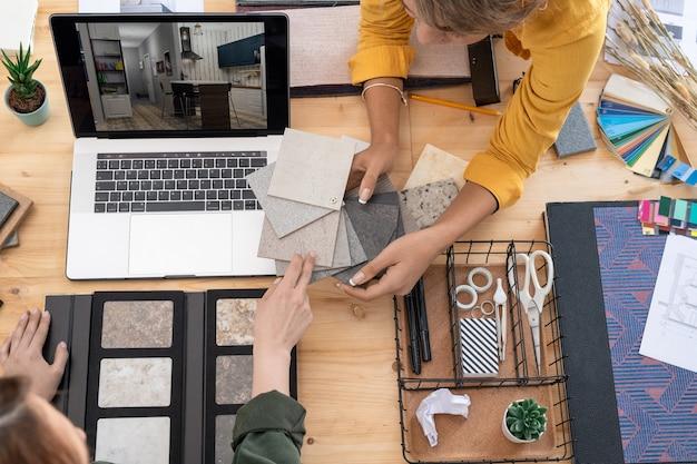 Due giovani designer di interni discutendo campioni di pannelli dal posto di lavoro mentre ne scelgono uno per le pareti della stanza sul display del laptop