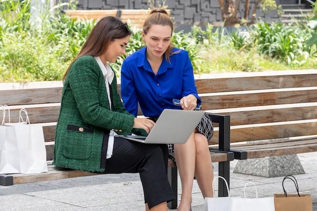 Due giovani dirigenti donne che controllano il loro laptop mentre chiacchierano dopo aver fatto acquisti con le borse della spesa