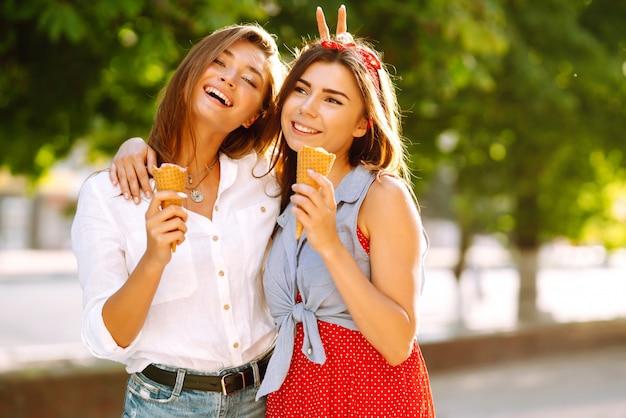 Due giovani amiche divertirsi e mangiare il gelato.