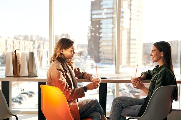 Due giovani acquirenti di sesso femminile con bevande seduti dalla finestra nella caffetteria all'interno del centro commerciale e chiacchierando sui loro ulteriori piani dopo lo shopping