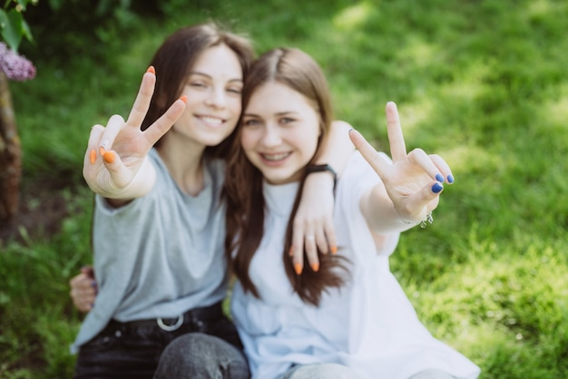 Due giovani adolescenti libere mostrano la pace del segno con le dita alla macchina fotografica e sorridono. messa a fuoco selettiva morbida, sfocatura.