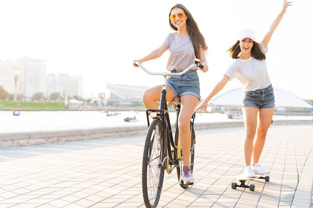 Due giovani amici che si rilassano in una calda giornata estiva con una giovane donna in bicicletta che rimorchia la sua amica su uno skateboard lungo una strada urbana