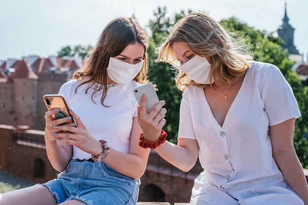 Due giovani amici che indossano maschere facciali e utilizzano i loro smartphone