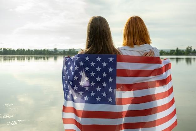 Due giovani amiche donne con la bandiera nazionale degli stati uniti sulle spalle in piedi insieme