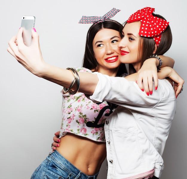 Due giovani donne divertenti che prendono selfie con il telefono cellulare Foto Premium