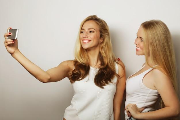 Due giovani donne divertenti che si fanno selfie con il cellulare