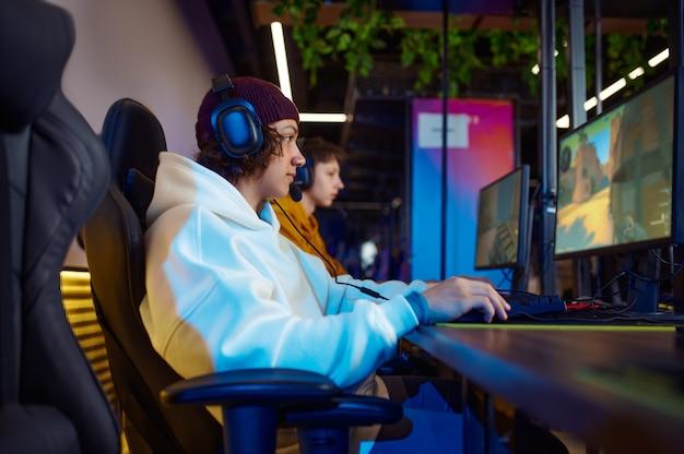 Due giovani giocatori in cuffia giocano in un club di videogiochi