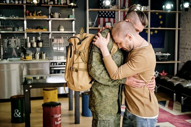 Due giovani gay in piedi abbracciati davanti alla telecamera