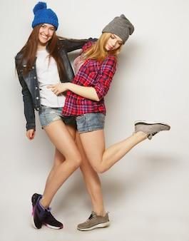 Due amiche che si divertono insieme. abbracciarsi e sorridere. stile hipster.