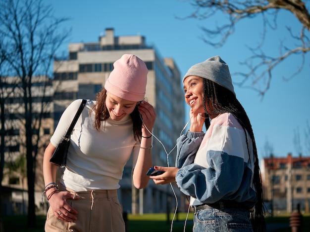 Due amici della ragazza che condividono un telefono cellulare tramite auricolari, all'aperto, che sembrano felici e sorridenti