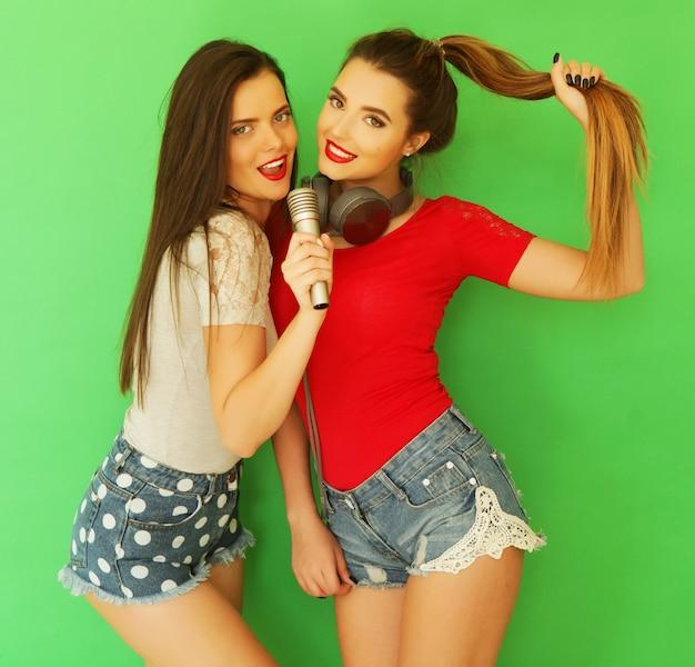 Due giovani amiche che stanno insieme e si divertono su sfondo verde