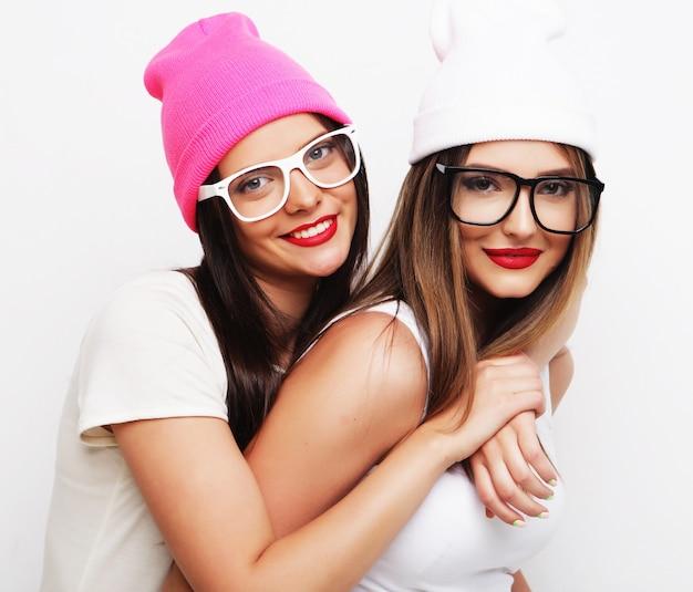 Due amiche che indossano cappelli in piedi insieme e si divertono.