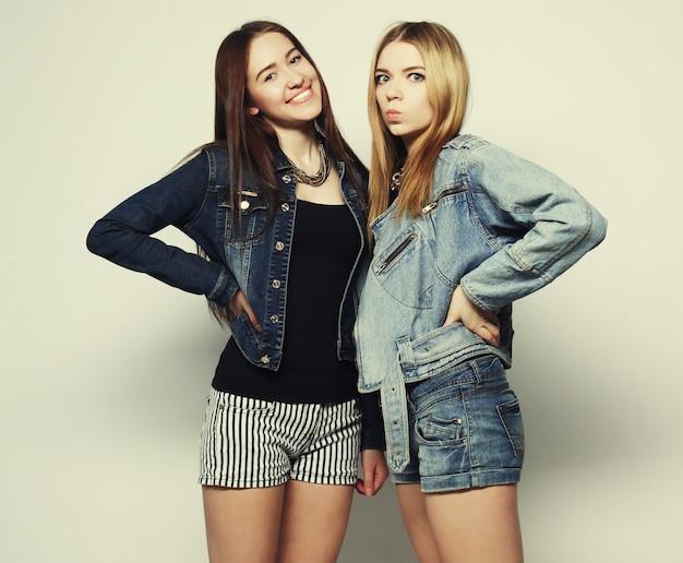 Due giovani amici hipster ragazza in piedi insieme, divertendosi. su sfondo grigio.