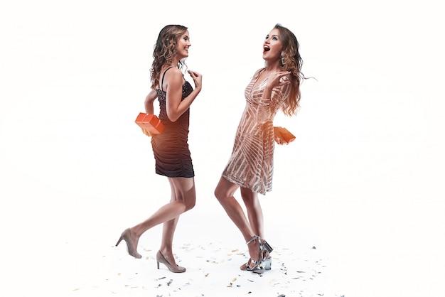 Due amici di ragazze che tengono i regali dietro la schiena per darli l'un l'altro.