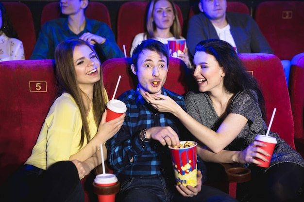 Due ragazze e un ragazzo che guardano una commedia in un cinema. giovani amici che guardano film al cinema. gruppo di persone in teatro con popcorn e bevande