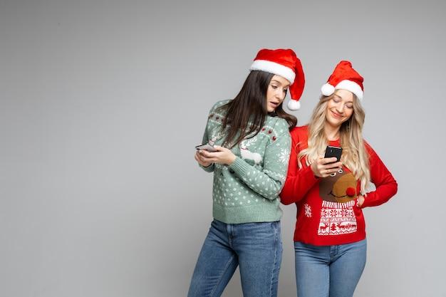 Due ragazze in cappelli di babbo natale e maglioni invernali fanno ordini, fanno acquisti online per telefono su sfondo grigio, copia spazio