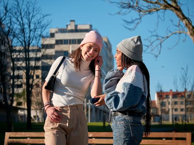 Due giovani ragazze condividono uno smartphone con auricolari per strada, in una giornata di sole, che sembrano felici e che indossano abiti casual