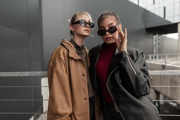 Due sorelle di giovani ragazze con occhiali da sole di moda in una giacca di pelle alla moda ed eleganti maglioni da magliaia in posa per strada vicino a un muro di metallo