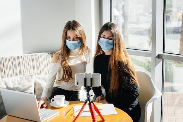 Due giovani ragazze si siedono in un caffè in maschera e dirigono un video blog. comunicazione alla telecamera.