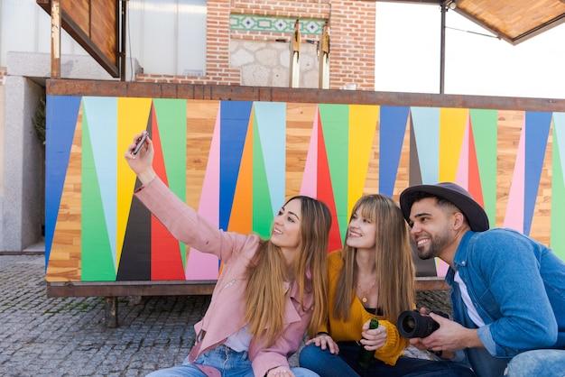 Due giovani ragazze scattano una foto con un telefono cellulare accanto a un ragazzo in possesso di una fotocamera digitale seduto sul pavimento con uno sfondo multicolore, luce naturale e spazio per il testo