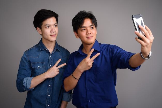 Due giovani uomini asiatici belli su grigio