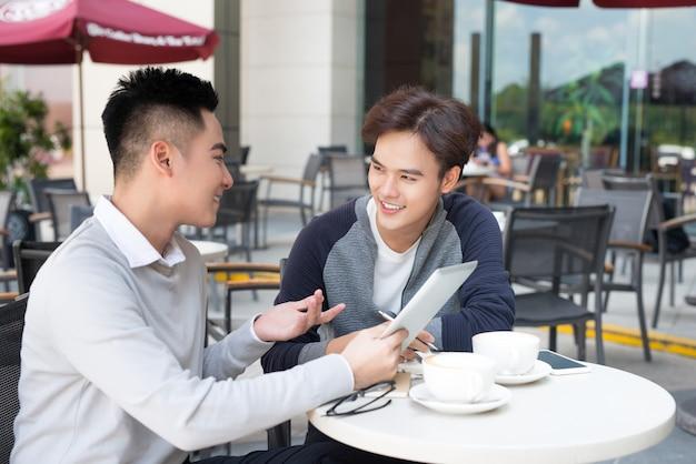 Due giovani uomini d'affari belli con un tablet che discutono del progetto