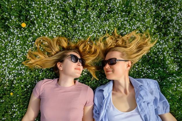 Due giovani ragazze felici con i capelli lunghi si trovano sull'erba verde in giornata di sole estivo e si guardano l'un l'altro. vista dall'alto: divertenti studentesse carine in occhiali da sole godono le vacanze nel parco.
