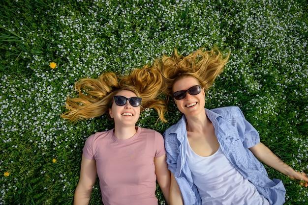 Due giovani ragazze felici con capelli lunghi si trovano sull'erba verde il giorno di estate soleggiato e sorridono alla macchina fotografica. vista dall'alto: divertenti studentesse carine in occhiali da sole godono le vacanze nel parco.