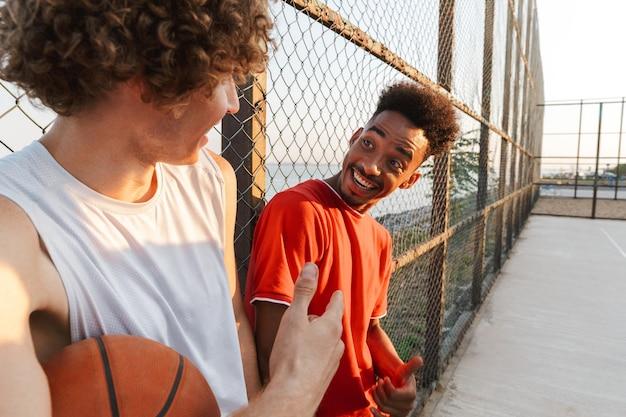 Due giovani giocatori di pallacanestro multietnici felici degli uomini