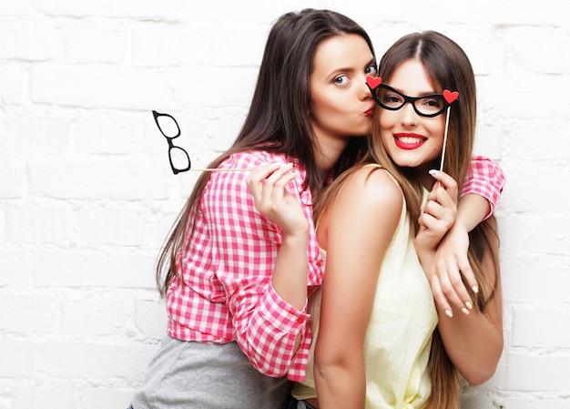 Due giovani donne felici con occhiali da festa che si fanno selfie