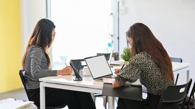Due giovani donne laboriose che lavorano in ufficio con dispositivi elettronici utilizzando laptop