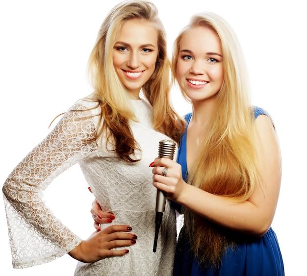 Due giovani ragazze bionde hipster che cantano, su sfondo bianco