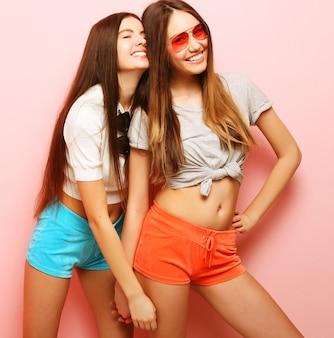 Due amici di ragazza giovani hipster in piedi insieme e divertirsi.