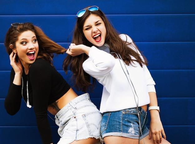 Due giovani amiche hipster insieme divertendosi. all'aperto, stile di vita.