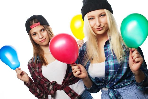 Due giovani ragazze hipster con palloncini