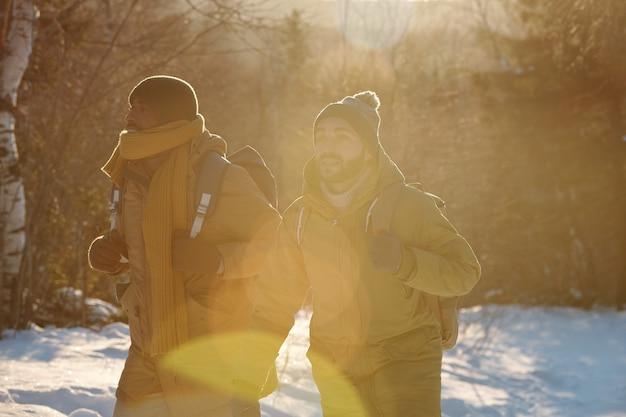 Due giovani backpackers interculturali che si muovono lungo la foresta invernale
