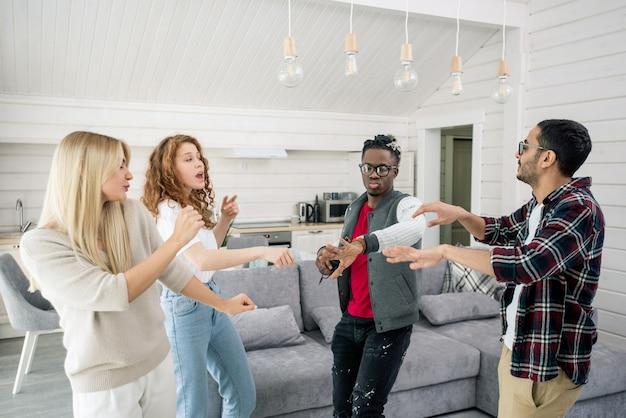 Due giovani coppie interculturali che si divertono a ballare insieme nel soggiorno a casa festa