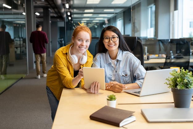 Due giovani donne manager interculturali con sorrisi a trentadue denti ti guardano mentre lavorano insieme sulla presentazione dal posto di lavoro in ufficio